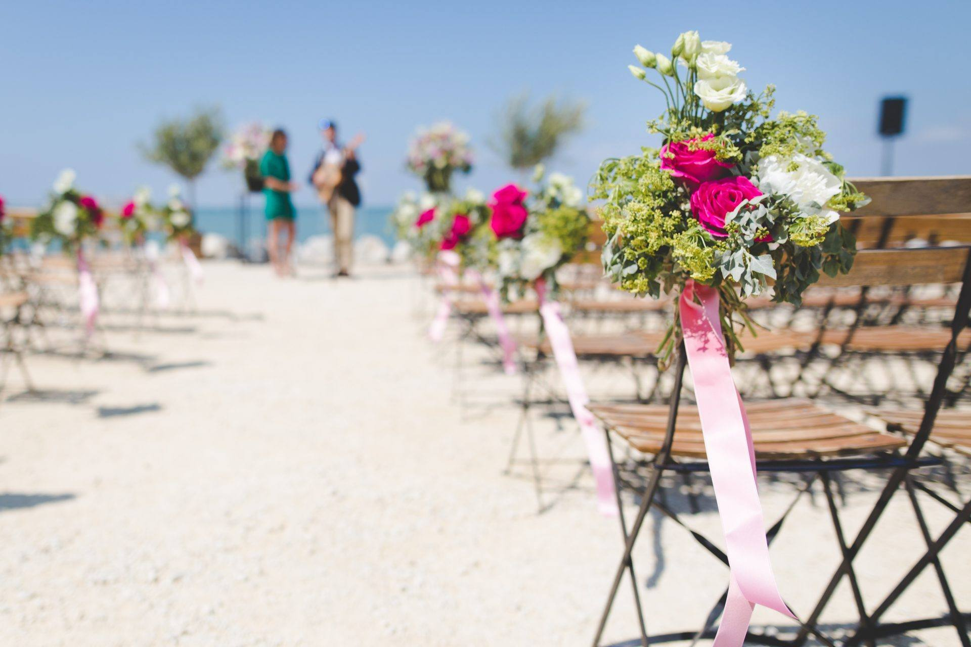 Destination wedding etiquette 101 flowers on guest chairs at beach wedding junglespirit Image collections