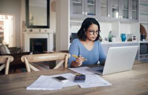 Woman at kitchen table with computer