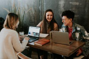 Three young people talk and laugh at a table with computers