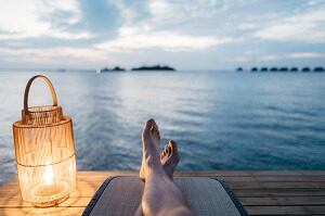 Person relaxing by water on a dock