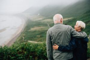 Older couple walking and looking out over the ocean
